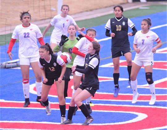 Abilene High's Gabby Stokes (12) and Jesenia Young battle Cooper goalie Nichole Cantu (0) and another Cooper player for the ball on a corner kick. AHS beat the Lady Cougars 4-0 in the nondistrict game Friday, Jan. 17, 2020, at Shotwell Stadium.