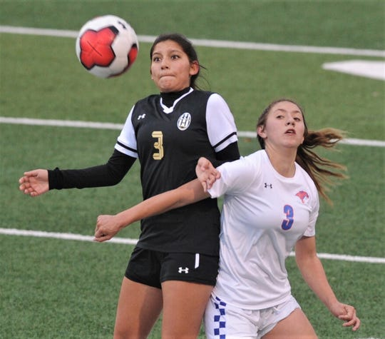 Abilene High's Madison Valencia, left, eyes the ball as Cooper's Victoria Damian battles for the ball, too. AHS beat the Lady Cougars 4-0 in the nondistrict game Friday, Jan. 17, 2020, at Shotwell Stadium.