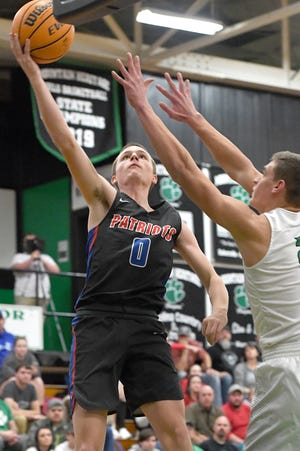 Madison's Alex Chambers goes up for a shot against Mountain Heritage's Logan Higgins during their game at Mountain Heritage High School on Jan. 17, 2020.
