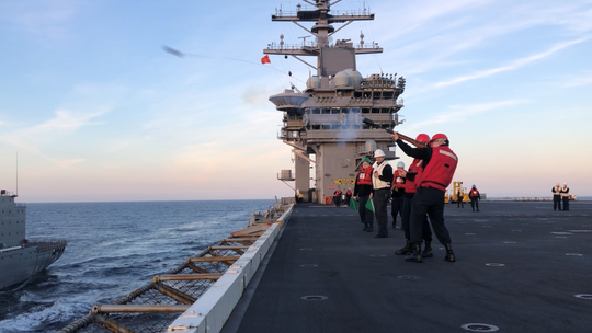 Christopher Nolen fires a 'projo,' a rubber bullet, from the USS Nimitz flight deck to the refueling ship Yukon. The rope attached will make it possible for the ship to take on hundreds of thousands of gallons of jet fuel.