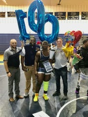 New Brunswick wrestler Keshon Davila with coaches (left to right) Joey Montuoro, Josh Davis and Ben Ostner after earning his 100th career win on Jan. 17, 2020