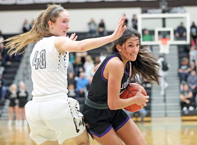 Johnston senior Kendall Nead (30) heads to the bucket past Ankeny Centennial senior Meg Burns (40) on Tuesday, January 14, 2020 at Ankeny Centennial High School.
