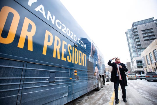 """Democratic presidential candidate Andrew Yang poses for a photo in front of his new campaign bus after speaking during the """"Women's Town Hall,"""" Saturday, Jan. 18, 2020, at the Englert Theatre in Iowa City, Iowa."""