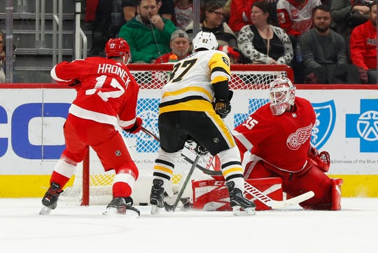 Sidney Crosby scores the winning goal against Jimmy Howard and Filip Hronek in overtime Friday at LCA.