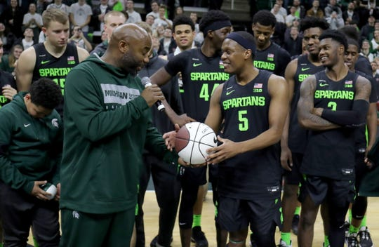 Mateen Cleaves presents Michigan State guard Cassius Winston with a ceremonial ball after Winston broke his assist record during the 67-55 win over Wisconsin at the Breslin Center in East Lansing, Friday, Jan. 17, 2020.
