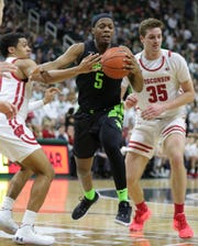 Michigan State's Cassius Winston passes against Wisconsin's D'Mitrik Trice (0) and forward Nate Reuvers (35) during the second half at the Breslin Center in East Lansing, Friday, Jan. 17, 2020.