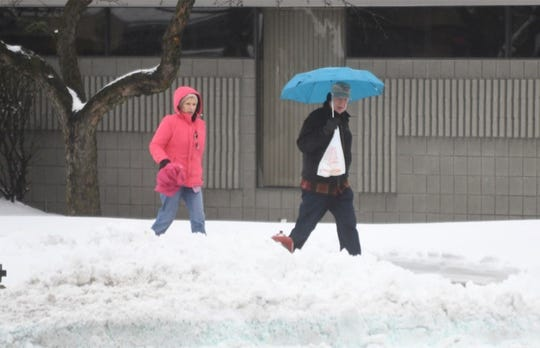 Pedestrians walk along 14 Mile Road near Main Street in Clawson as rain begins to fall after an early morning snow storm on Saturday, January 18, 2020.