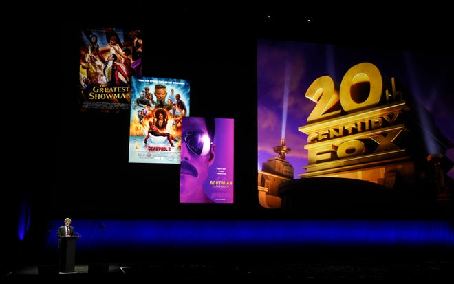 Alan Horn, chairman of The Walt Disney Studios, speaks underneath poster images for 20th Century Fox films during the Walt Disney Studios Motion Pictures presentation at CinemaCon 2019.