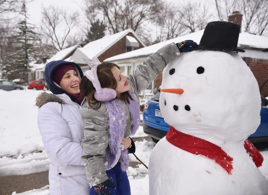 Sara Filthaut, left, of Huntington Woods builds a snowman with her daughter Brooklyn on their front yard along Lincoln Street in Huntington Woods on Saturday, January 18, 2020.
