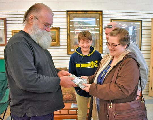 In this Jan. 16, 2020 photo, Howard Kirby, left, gives $43,170 to Kim Fauth-Newberry at a resale store in Owosso Township.