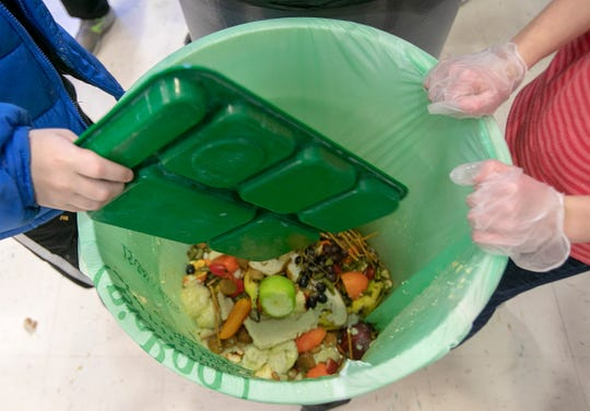 Students discard food at the end of their lunch period as part of a lunch waste composting program at Thalberg Elementary School in Southington, Conn., Wednesday, Jan. 15, 2020.
