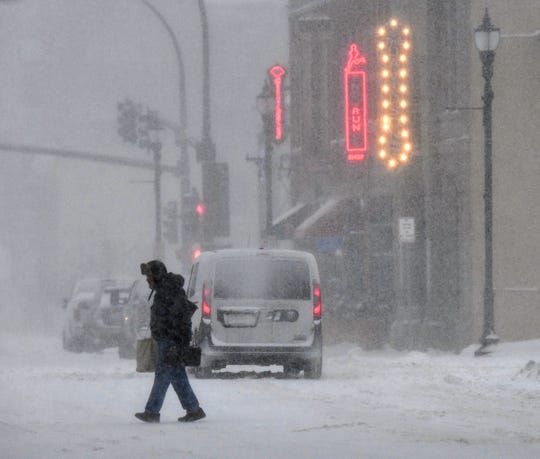 Heavy snow falls as people make their way home after work in downtown St. Cloud, Minn., Friday, Jan. 17, 2020.