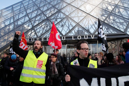 Striking employees demonstrate outside the Louvre museum Friday, Jan. 17, 2020 in Paris.