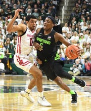Badgers' D'Mitrik Trice defends against Spartans' Cassius Winston in the first half.