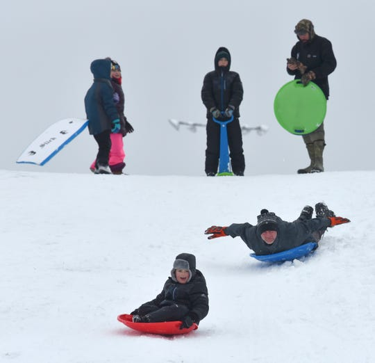 Alan Hanna follows Owen Bonior, 6, both of Mount Clemens, as they sled close to their home.