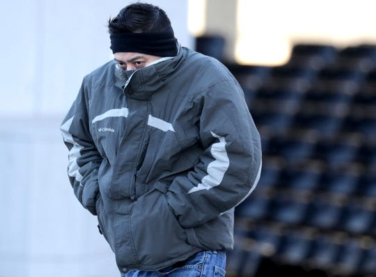 Jorge Hernandez, of Milwaukee, tries to cover his face from the cold while walking along West Kilbourn Avenue in Milwaukee, Thursday, Jan. 16, 2020.