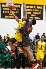 Detroit King's Omar Zeigler (1) takes a shot while closely guarded by Frederick Douglass' Frankin Ezeoka (2) during the first half.