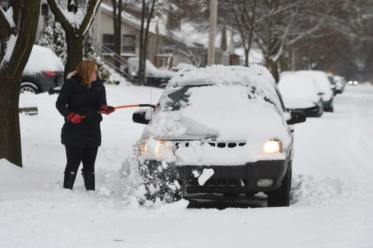 Keely Crimando of Ferndale brushes snow off her Jeep along E. Lewiston Street in Ferndale on Saturday, January 18, 2020.