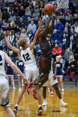 Bosse's Kiyron Powell (52) goes up to the net as Reitz's Owen Dease (12) guards him during the Banterra Bank SIAC Tournament semifinal at Reitz High School in Evansville, Ind., Friday, Jan. 17, 2020.