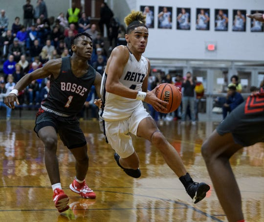 Reitz's Khristian Lander (4) drives past Bosse's Ty'Ran Funches (1) during the Banterra Bank SIAC Tournament semifinals at Reitz High School in Evansville, Ind., Friday, Jan. 17, 2020. The Bosse Bulldogs defeated the Reitz Panthers, 93-73.