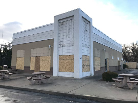 """The building that formerly housed a KFC restaurant, at the corner of U.S. 41 and Covert Avenue, has been boarded up with all KFC signage removed. A piece of copy paper taped to the door reads simply """"Permanently closed."""""""