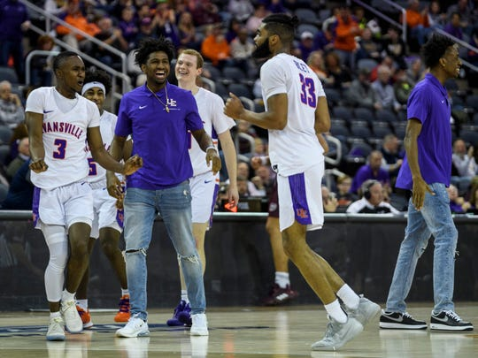 Evansville's Jawaun Newton (3) and new transfer Samari Curtis cheer on Evansville's K.J. Riley (33) during the first half at Ford Center in Evansville, Ind., Saturday, Jan. 18, 2020. The Purple Aces fell 68-58 to the Bears.