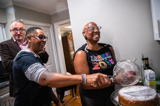 As Upstate Pride President Rodney Tow looks on, the group's diversity officer, Terena Starks, sprinkles sugar onto a cake with fellow Upstate Pride board member Caroline Caldwell at a dinner party at Caldwell's home in Greenville on Friday, Jan. 17, 2020.