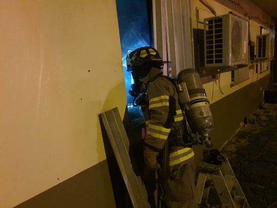 A Guam Fire Department firefighter surveys the inside of a home after flames were extinguished inside a bedroom on Friday, Jan. 17, 2020.