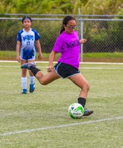 Players of Team Bumachacha, in purple, compete against Team Raiders Blue during the first-ever Guam Football Association 8v8 Maga'haga All-Girls Soccer Tournament at the GFA National Training Center in Dededo on Saturday, Jan. 18, 2020.