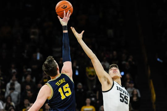 Michigan center Jon Teske and Iowa center Luka Garza battle for the opening tipoff Friday at Carver-Hawkeye Arena. The two big men battled throughout a high-scoring Big Ten Conference basketball game.