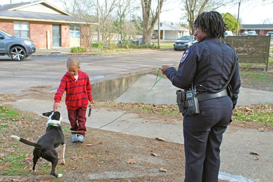 In this Jan. 9, 2020 photo, Starkville Police Officer Angelica Colbert, right, takes Star Gazer around town as part of the Dog's Day Out program to facilitate community engagement in Starkville, Miss.  The program, which began in November, allows anyone to pick up a dog for a few hours and take it on a walk or another outing. Colbert took a brown pit bull named Lola around town with her, from police headquarters to Main Street and a few neighborhoods, she said.
