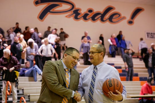Harrison head coach Mark Rinehart shares a moment athletic director Jerry Galema after Harrison defeated Kokomo, 58-37, to earn Rinehart 100th win at Harrison, Friday, Jan. 17, 2020 in West Lafayette.