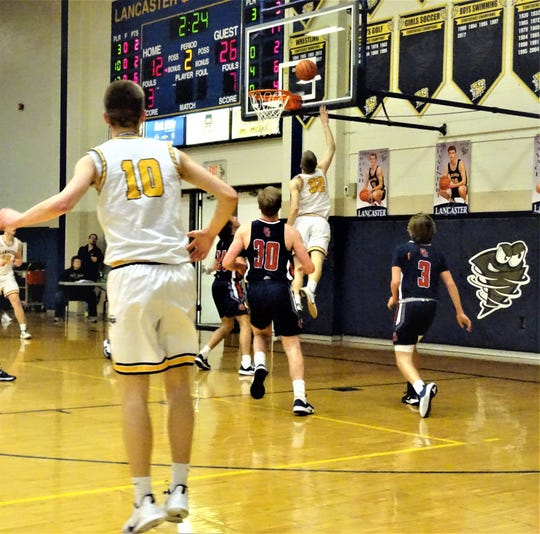 Lancaster's Tanner Roush lays in a shot against Grove City Friday night. The Golden Gales fell shot, 66-38.