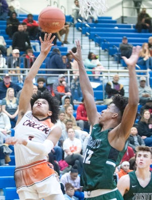 Fern Creek guard Jaden Rogers uses the backboard to score avoiding Trinity guard Cam McClain in the second semifinal game of the Boys LIT tournament. 17 January 2020