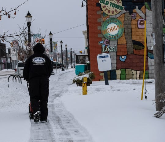 A man uses a snow blower to clear the sidewalk in Lansing's Old Town Saturday, Jan. 17, 2020.