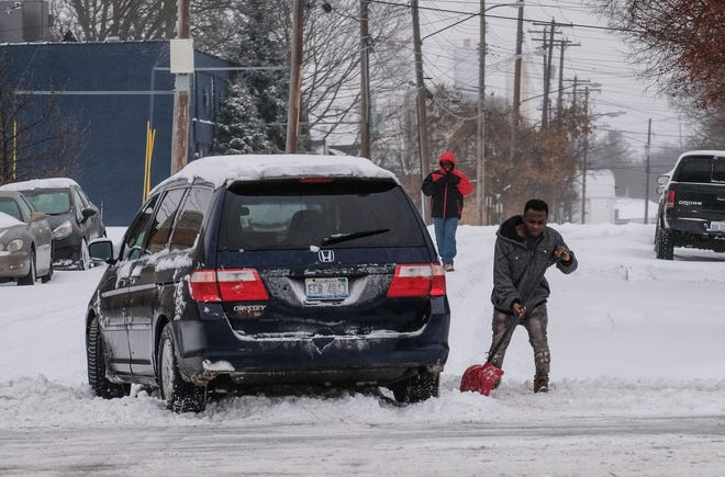 A man tries to dig his car out from stuck in a pile of snow left by a plow as he tried to turn off of Cesar Chavez Avenue in Lansing. He got a push from a good samaritan and was able to drive off Saturday, Jan. 17, 2020.