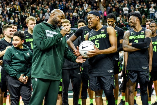 Former Michigan State great Mateen Cleaves, left, gives Cassius Winston a commemorative ball to Winston who passed Cleaves' Big Ten career assist record with 817 during a ceremony for Winston after the Spartans game against Wisconsin on Friday, Jan. 17, 2020, at the Breslin Center in East Lansing.