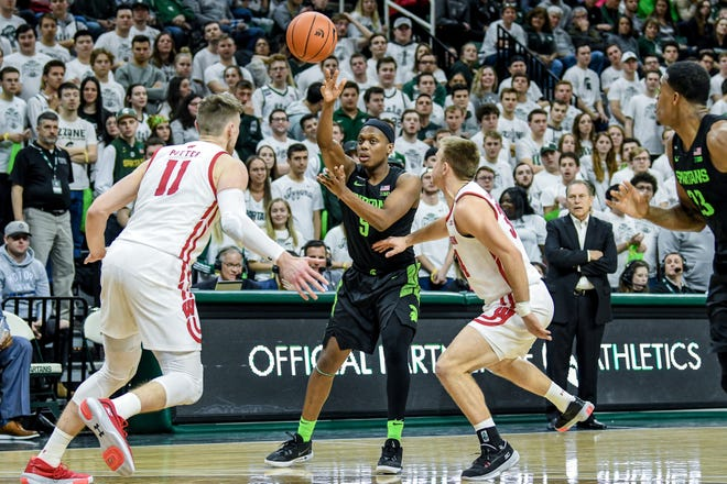 Michigan State's Cassius Winston passes the ball to Xavier Tillman for an ally-op dunk during the second half on Friday, Jan. 17, 2020, at the Breslin Center in East Lansing. The assist was Winston's 817th of his career. Winston broke the Big Ten assist record on the play previously held by MSU great Mateen Cleaves.