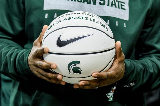 Former Michigan State great Mateen Cleaves holds a commemorative ball for Cassius Winston who passed Cleaves' Big Ten career assist record with 817 during a ceremony for Winston after the Spartans game against Wisconsin on Friday, Jan. 17, 2020, at the Breslin Center in East Lansing.