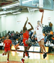 Ashland's Luke Denbow goes for a layup as Mansfield Senior's Maurice Ware tries to block the shot.