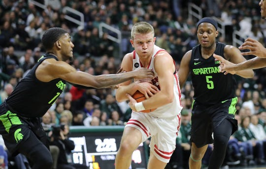 Wisconsin's Brad Davison drives to the basket and draws a foul from Michigan State's Aaron Henry (11)  at the Breslin Center on Friday night.