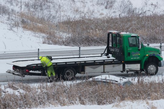 A flatbed truck operator prepares to tow a motorist who spun off the road Saturday on I-41 in Lomira.