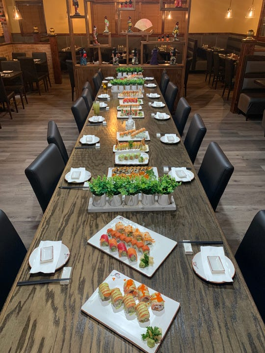 Seating at Jin's Sushi Seafood & Bar includes a large communal table. Besides tables, seating is available at the sushi bar and cocktail bar.