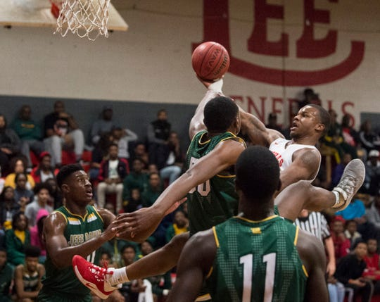 Lee's Jamari Smith (1) is fouled by Jeff Davis' Ja'Corey Robinson (50) as he makes an and-one play at Robert E. Lee High School in Montgomery, Ala., on Friday, Jan. 17, 2020.