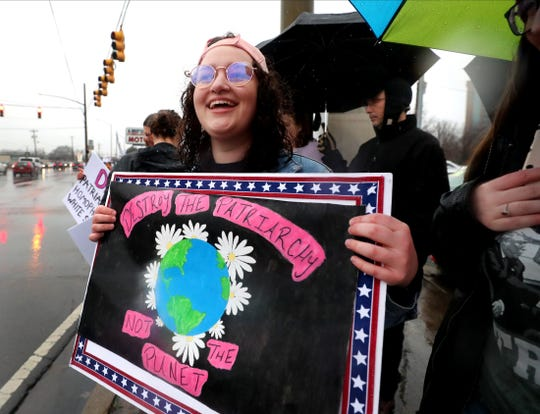 Julianne Richardson holds a sign on the corner of Broad and Church Streets as she participates in the 2020 Women's March organized by Power Together Tennessee, on Saturday, Jan. 18, 2020, in downtown Murfreesboro, Tenn.