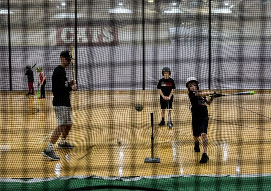 Will Bolte works on his hitting Saturday with Newark senior Logan Swonger, during the annual baseball camp at Newark High School hosted by professional pitcher Derek Holland.