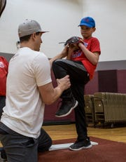 Newark graduate and Major League pitcher Derek Holland helps Luke Davis with his technique Saturday during Holland's annual baseball camp at Newark High School.