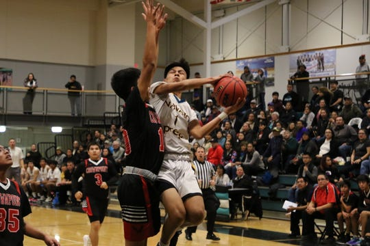 Navajo Prep's Isaiah Morris attacks the basket against Crownpoint during Friday's District 1-3A boys basketball game at the Eagles Nest in Farmington.
