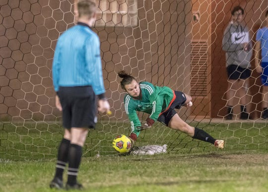 Raiders goalie Korey Betts (1) dives to make a save on a Dolphins penalty kick to keep the score 1-0 in his favor during the Gulf Breeze vs Navarre boys soccer game in Navarre on Friday, Jan. 17, 2020.