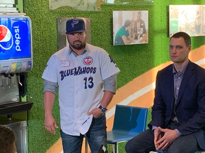 Blue Wahoos manager Ramon Borrego with Alex Hassan, the Minnesota Twins director of minor league development, while introducing the Wahoos' patch to honor NAS Pensacola shooting victims.